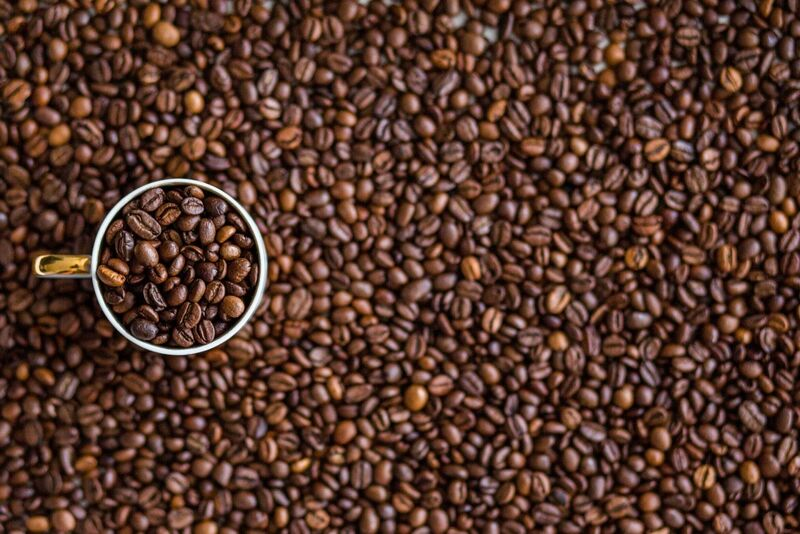 Softs - Cup of Roasted Coffee Beans on Pile